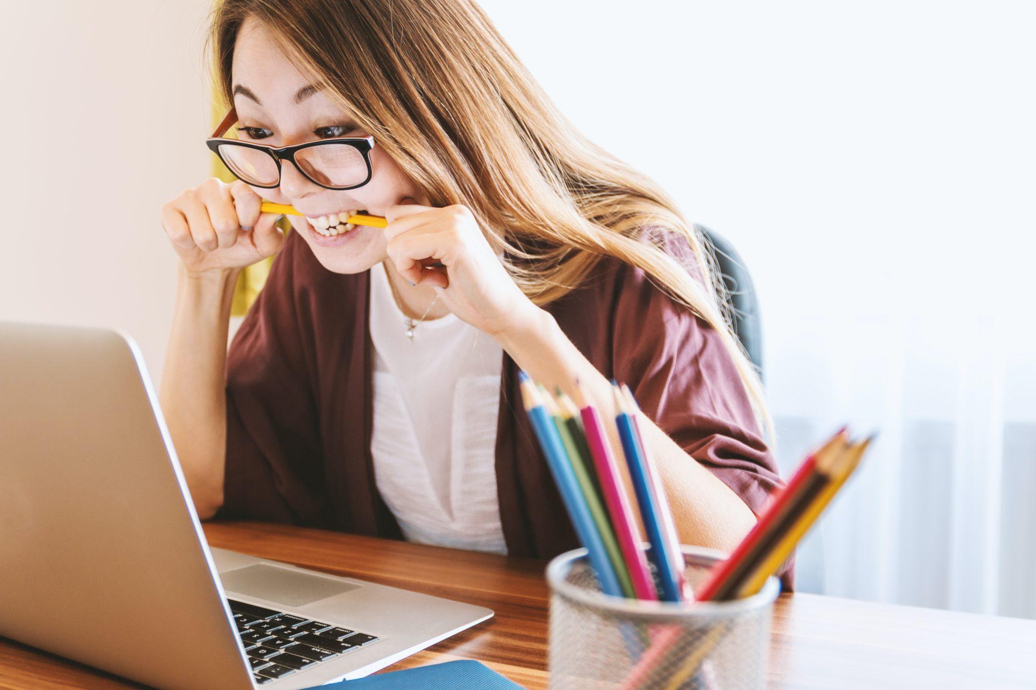 woman biting on pencil looking at computer