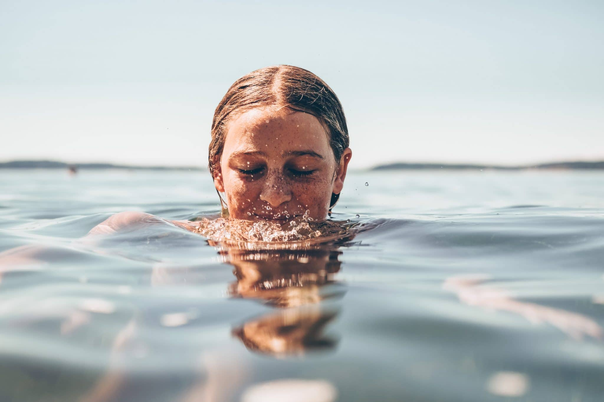 woman with her head half way in water