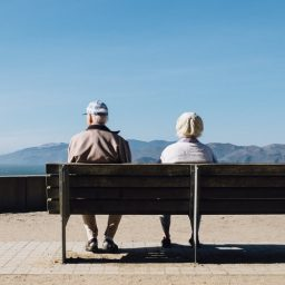 Two elderly seniors sitting on a bench