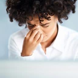 Woman experiencing sinus pressure from allergies.